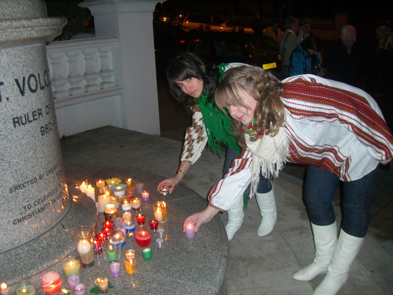 Maryana Tuka, 17, and Solomia Boretska, 16, place candles in front of the statue of St. Volodymyr the Great in London's Holland Park. Photo by Christina Paschyn, London, 2007.